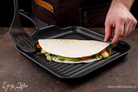 Аккуратно заверните лепешку и обжарьте на сковороде-гриль с обеих сторон.
