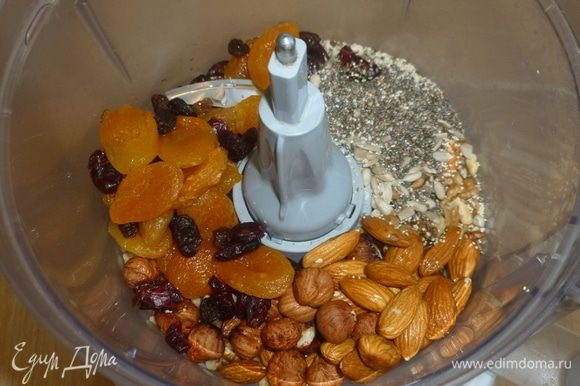 Духовку разогреть до 190°C. В комбайн сложить: орехи, семена, сухофрукты, специи и натереть цедру с апельсина. Измельчить.