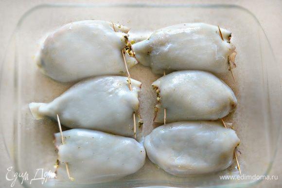 Тушки кальмаров наполните приготовленной начинкой, отверстия закрепите зубочистками.
