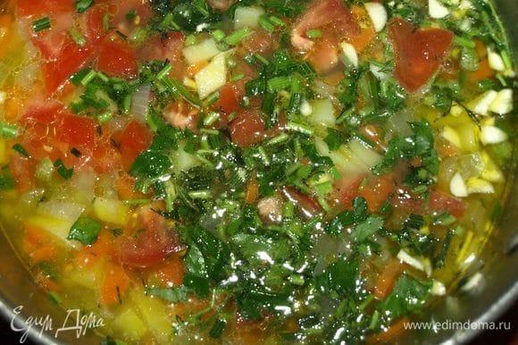 Добавить в кастрюлю помидоры, стебли зелени, чеснок и варить до мягкости картофеля.