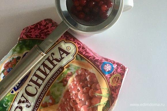 Пока готовится нижняя половина омлета, есть время заняться соусом. Для него я использовала бруснику, которую заранее разморозила. Половину из указанного количества ягод я перетерла через ситечко, вторую половину ягод оставила целенькими. Соединила перетертое брусничное пюре, целенькие ягоды, добавила сок после разморозки, сахарную пудру и немного уварила.