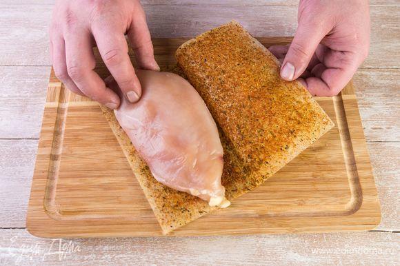 Положите отбитую грудку на половину листа MAGGI®, закройте второй половиной и прижмите рукой.