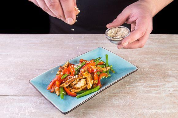 Разложите салат по тарелкам и посыпьте кунжутом.