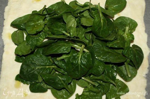 Тесто заранее разморозить. Вытянуть пласт руками. Выкладываем на пласт промытый шпинат, сбрызгиваем оливковым маслом.