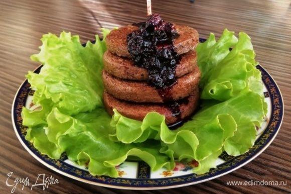Для одной порции уложите 4 печеночных оладья друг на друга и скрепите шпажкой. Полейте черничным соусом. Можно подавать.
