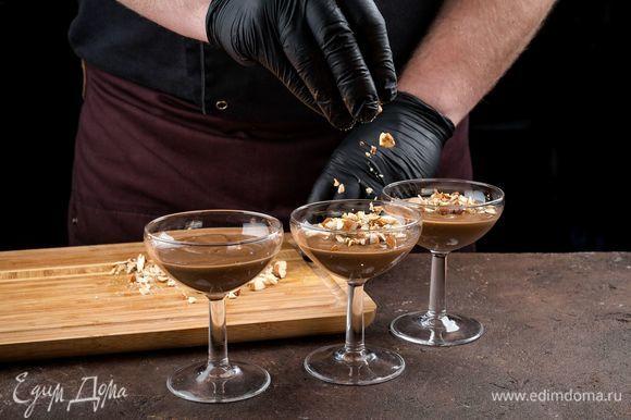 Ложкой переложите в креманки или небольшие стаканы шоколадный мусс, украсьте миндалем.