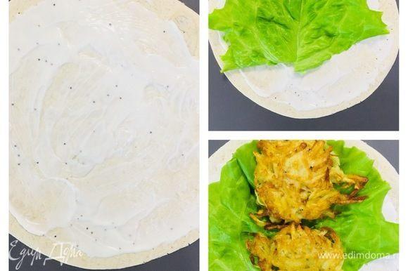 На лаваш равномерно наносим сырный соус, выкладываем листья салата, хашбраун.