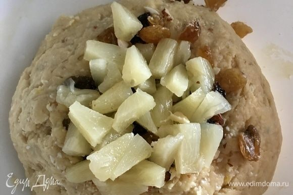 В тесто добавить орехи, изюм и ананасы. Тщательно вмешать их в тесто.