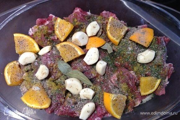 Сверху на мясо — чеснок, апельсин (да и дольки мандарина пойдут), травок разных (тут смесь кавказских и хмели-сунели), лаврушка.