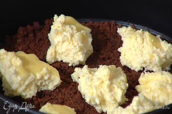 Из остывшего чизкейка ложкой для мороженого вырезать небольшие кусочки и разложить на охлажденном корже.