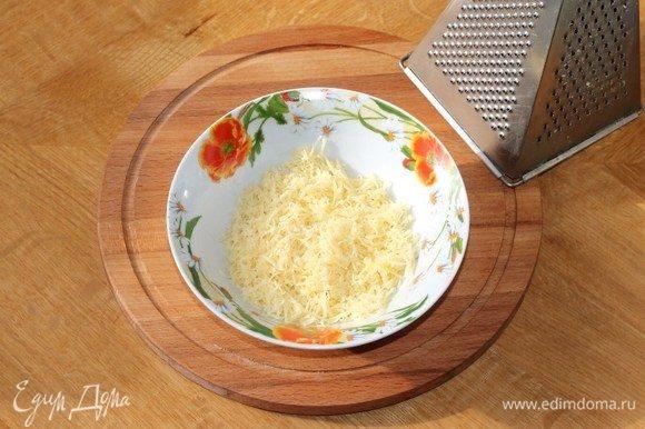 Приготовим начинку. Сыр натереть на средней терке. Три столовые ложки отделить от общей массы.