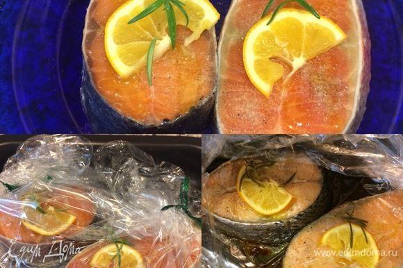 Духовку нагреть до 180–200°C. Стейки вымыть, обсушить бумажным полотенцем, посыпать солью, белым перцем и полить слегка маслом. Стейки положить в рукав для запекания, сверху положить лимон, розмарин, рукав затянуть и отправить в духовку на 15–20 минут. Перед тем, как достать готовую рыбку, можно разрезать рукав и дать ей слегка подрумяниться.