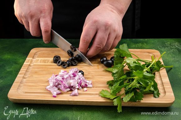 Отварите яйца вкрутую. Лук и петрушку измельчите. Нарежьте колечками маслины. Каперсы промойте от соли и обсушите.