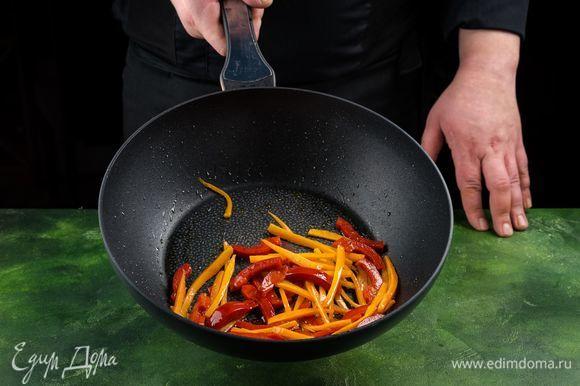 Смажьте сковороду оливковым маслом и обжарьте перец и морковь на сильном огне в течение минуты.