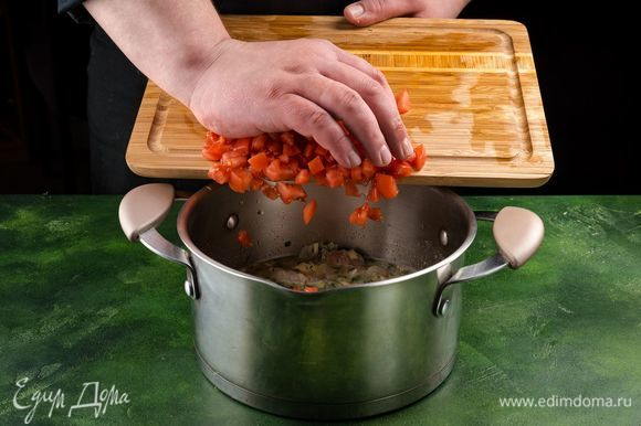 Добавьте в кастрюлю часть масла с чесноком и зеленью, а также помидоры. Как только масло разойдется, снимите кастрюлю с огня.