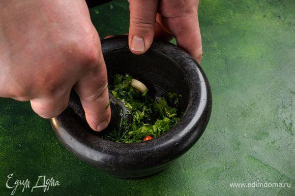 Приготовьте соус. Зелень промойте и порвите руками. Очистите чеснок и перец чили. В ступку сложите зелень, чеснок, перец, посолите, добавьте растительное масло и лимонный сок. Все хорошо разотрите.