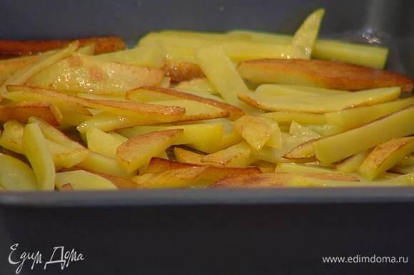 Обжаренный картофель переложить в глубокий противень и запекать в разогретой духовке 15‒18 минут.