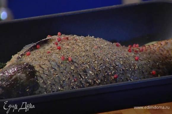 Один лавровый лист и половину тимьяна поместить в брюшко карпа, оставшийся лавровый лист и веточки тимьяна разложить вокруг рыбы, посыпать ее внутри и снаружи специями.