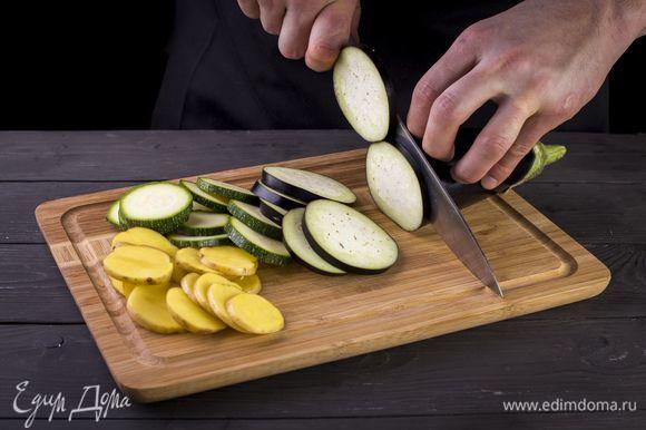 Нарежьте картофель, баклажан и цукини кружочками.