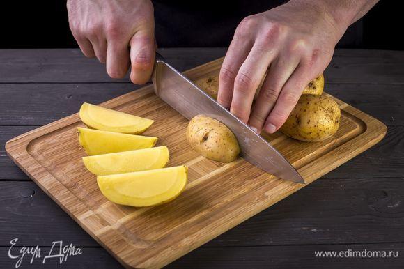 Клубни картофеля тщательно промойте со щеткой, проварите в кипящей воде 5–7 минут. Нарежьте картофель на дольки.