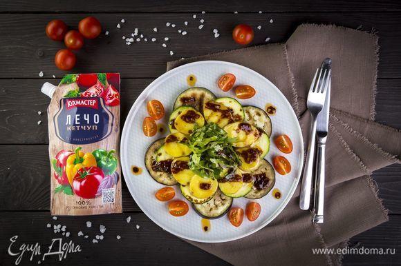 Выложите теплые овощи на блюдо слоями, полейте томатным соусом. Украсьте салат четвертинками черри и листьями руколы.