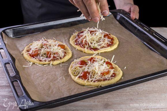 Выложите слой из ломтиков ветчины, посыпьте тертым сыром, украсьте черри и оливками.