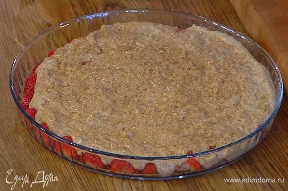 Разрезать пополам 500 г клубники и выложить в большую форму для выпечки плоской стороной вниз, сверху равномерно распределить миндальную массу и выпекать в разогретой духовке 20 минут.