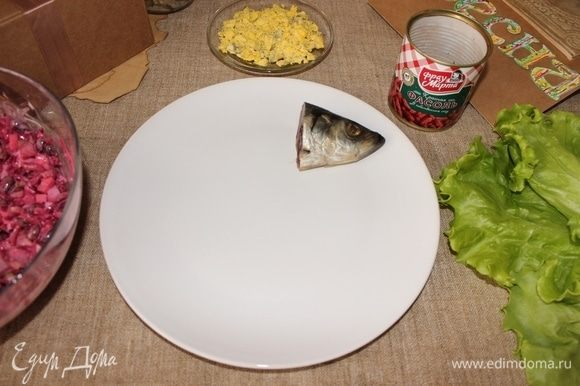 Часть салата сделаем в виде фрау сельди, выкладываем голову от сельди на тарелку.