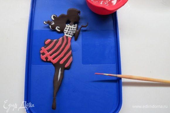 Шоколадную фигурку можно раскрасить какао-маслом. Для этого растапливаем какао-масло в микроволновке, окрашиваем его жирорастворимым красителем и кисточкой наносим рисунок на шоколад.