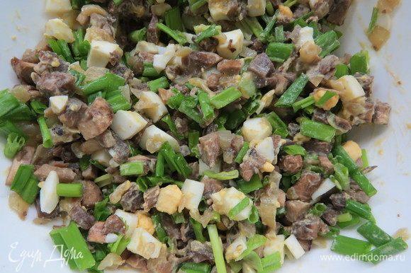 Мелко нарезать перья зеленого лука, добавить нарезанный зеленый лук и вареные яйца к обжаренным грибам.