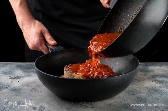 К овощам выложите стейки. Залейте все томатным соусом и готовьте до мягкости мяса.
