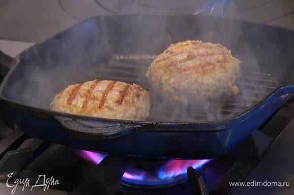 Разогреть сковороду-гриль, смазать ее оливковым маслом, выложить бургеры и, накрыв крышкой, жарить с одной стороны до появления золотистой корочки, затем котлеты перевернуть, влить немного воды и, снова накрыв крышкой, жарить до готовности.
