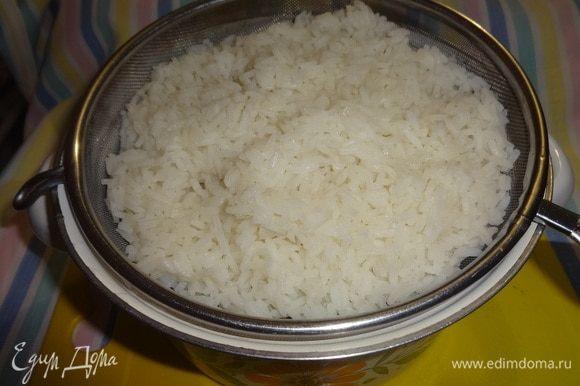 Отваренный рис откинуть на дуршлаг. Затем выложить в кастрюлю.