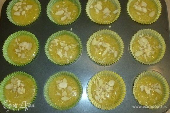 Разложить тесто по формам, заполняя их на 3/4, посыпать миндльными лепестками и выпекать 15–20 минут до золотистого цвета.