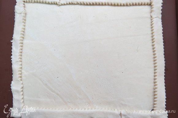 Пласт слоеного теста раскатать на силиконовом коврике или бумаге для выпечки, по периметру сделать бортики.
