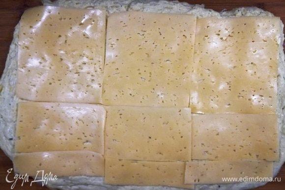 Растягиваем руками тесто в пласт и выкладываем пластинки сыра «Гауда». Можете взять плавленый сыр. Тоже будет вкусно.