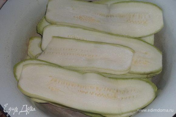 Выложить кабачки в миску слоями, посыпая каждый слой небольшим количеством соли. Дать кабачкам постоять 15–20 мин.