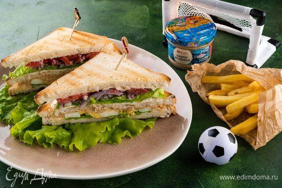 Накрываем оставшимся куском хлеба, смазанным сыром. Разрезаем каждый сэндвич на 2 части по диагонали, каждую часть закалываем шпажкой. Подаем с картофелем фри (по желанию). Футбольные фанаты будут рады такой сытной закуске!