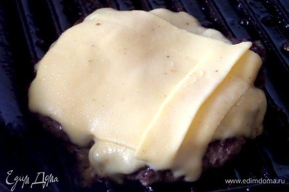Котлетку перевернуть и перенести пластинками сыр сверху 2–3 ломтика.