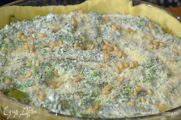Подпеченное тесто в форме посыпать половиной оставшегося натертого сыра, разложить нарезанный лук, спаржу и зеленый горошек, залить все творожной массой с зеленью, посыпать оставшимся сыром и кедровыми орехами.