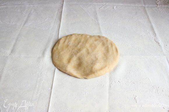 Положить лепешку из теста на скатерть, посыпанную мукой.