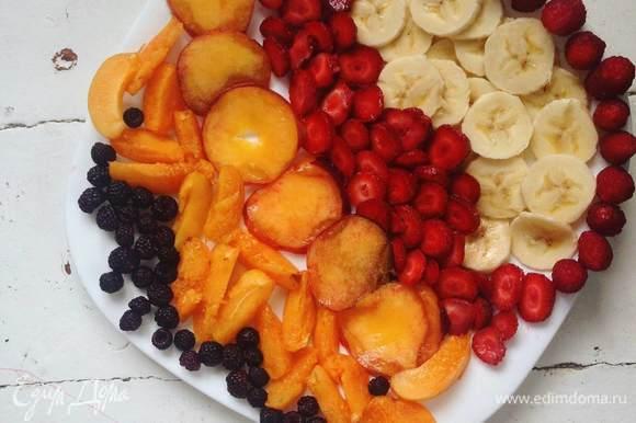 Смазываем форму маслом, кладем шарик теста на дно и раскатываем пальцами, формируя бортики по бокам и «тарелочку» посередине. Смазываем дно «тарелки» ряженкой или жирными сливками. Выкладываем фрукты и ягоды, ставим в разогретую до 200°C духовку.