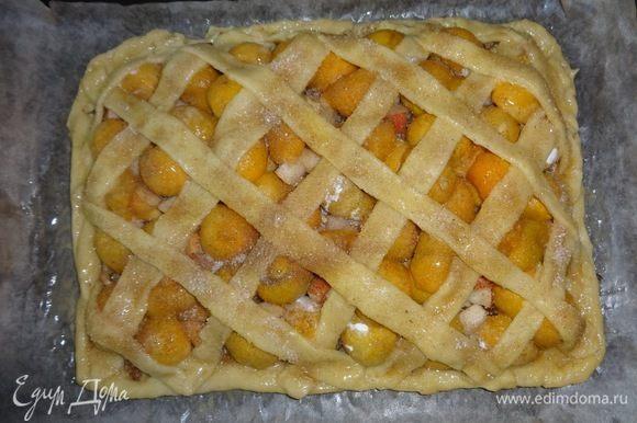 Яйцо взболтать. Смазать яйцом незаполненные начинкой края пирога. Затем уложить полоски по диагонали, сначала в одном направлении, затем — в противоположном, прижимая их к краям. Полоски также смазать яйцом. Соединить сахар и корицу, посыпать пирог сверху.