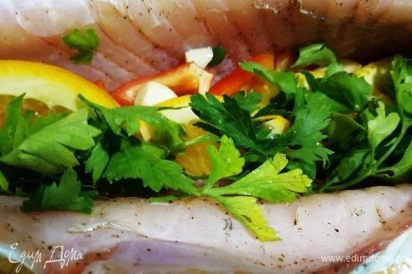 Рыбу солим и перчим внутри и снаружи. В брюшко укладываем несколько долек лимона, дольку апельсина, немного болгарского перца и помидора, петрушку.