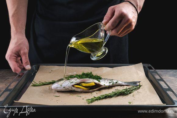 Рыбу положите на противень для запекания, застеленный пергаментом. Посыпьте сверху укропом, сбрызните оливковым маслом, рядом положите веточки розмарина. Запекайте дораду при 200°С 20 минут.