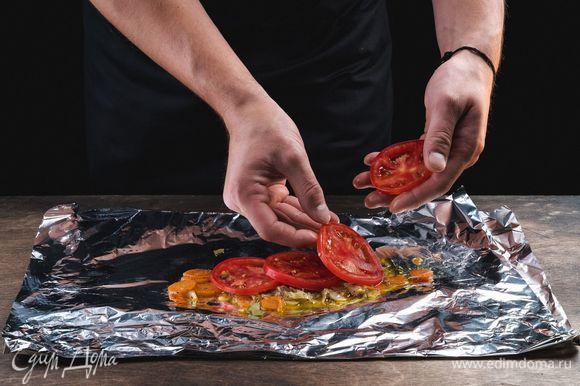Выложите приготовленные овощи в конвертик из фольги, сверху положите часть нарезанного помидора.