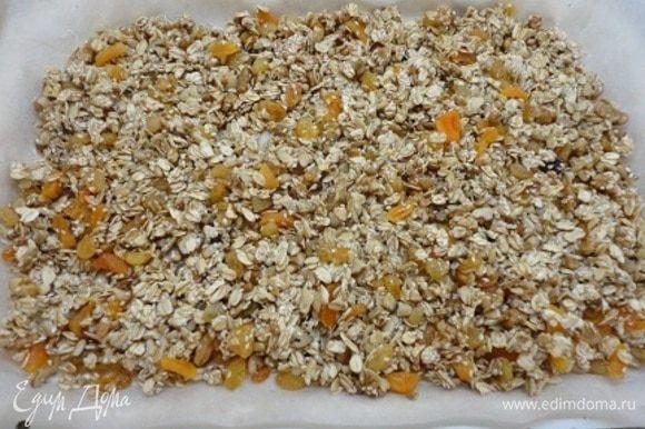 Противень выстилаем бумагой, смазываем ее сливочным маслом и равномерно распределяем смесь по поверхности.