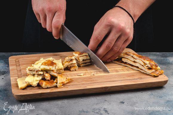 Приготовьте омлет. Для этого смешайте яйца, тертый сыр, сливки и поджарьте омлет на оливковом масле с обеих сторон. Омлет остудите и нарежьте небольшими полосками.