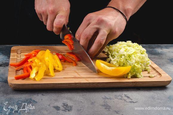 Пекинскую капусту и болгарский перец нарежьте тонкой соломкой.