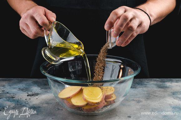 В емкости соедините оливковое масло, соль, перец, тмин. Замаринуйте картофель на 15 минут.